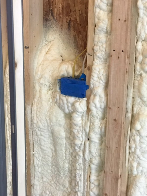 Using Spray Foam for a Country Home - electrical boxes taped to keep foam out